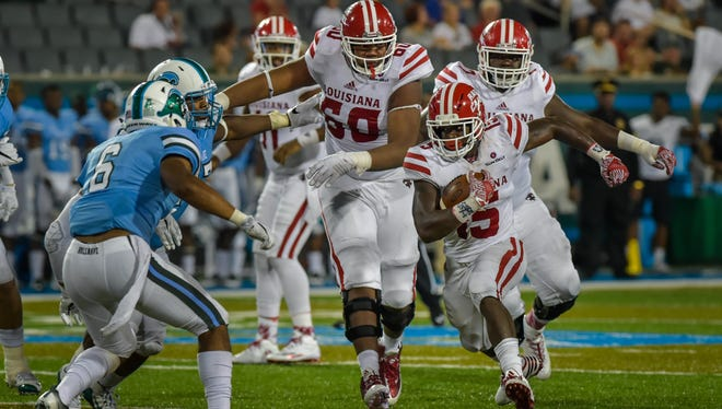 UL's Elijah McGuire runs in front of tackle D'Aquin Withrow (60) on one of his 38 carries in Saturday's loss at Tulane.
