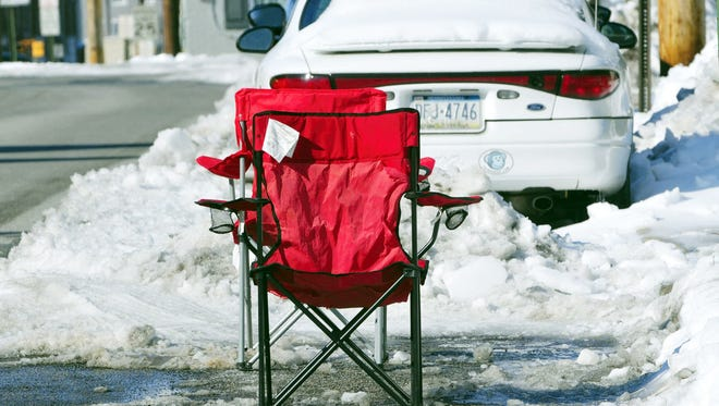Folding chairs mark a parking space on Feb. 7 that a resident dug out after a snowstorm in Chambersburg, Pa.