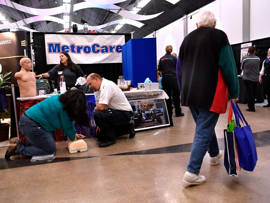 MetroCare Services paramedic Kenny Dennis watches Eva Foster practice CPR on a training dummy during Wednesday's Business EXPO at the Abilene Convention Center.