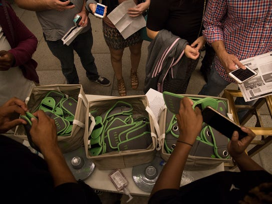 Event-goers line up as their mobile devices are locked