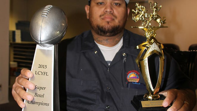 Luna County Youth Football League Commissioner Cesar Moreno holds the Super Bowl team trophy and the individual trophy that will be awarded to each of the Super Bowl Champions following Saturday's post season finale at Deming High School Memorial Stadium.