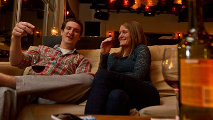 Jennifer Keleman, 28, and her fiance, nestled together on an oversized sofa, clink their wine glasses.