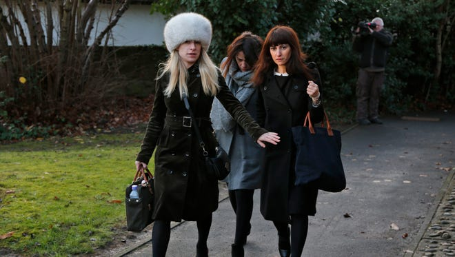 Italian sisters Francesca, right, and Elisabetta Grillo, background center -- former personal assistants of English broadcaster Nigella Lawson and her former husband, art collector Charles Saatchi -- arrive at the Isleworth Crown Court, in west London, on Dec. 20, 2013, during a trial over alleged fraud.