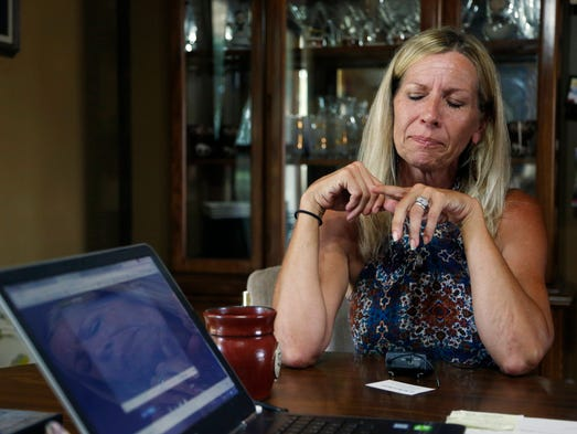 Cyndi Mouw gets emotional as she looks at the video
