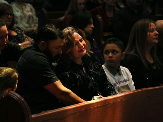 Carla Gabrielle Ballesteros' mother Connie Elizalde, middle, cries during her daughter's funeral at the Saint Therese Church of the Little Flower in Reno on May 31, 2018. Elizalde's husband  Jesus is seen on the left comforting her as her son Carlos Ballesteros looks on from the right.