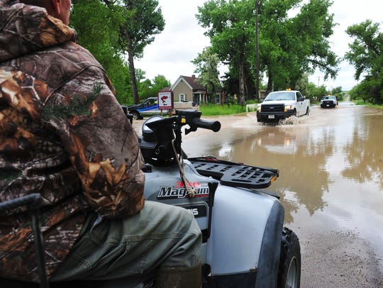 County vehicles drive through flood water on Sun River-Cascade