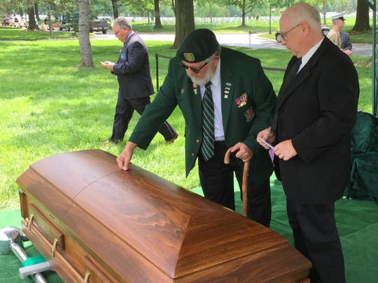 James C. Johnson, left, places a penny on the casket of his uncle, Marine Pfc. James B. Johnson, who was buried at Arlington National Cemetery on May 31, 2016. Another nephew, John McManus, stands next to the casket.