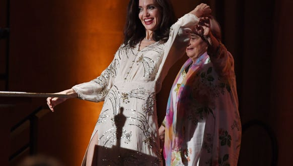 Angelina Jolie (L) dances with French director Agnes