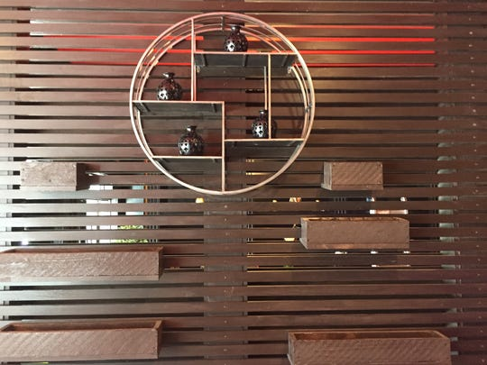 At the entrance to Creazian, a formerly solid wall is now a slatted partition hung with decorative elements.