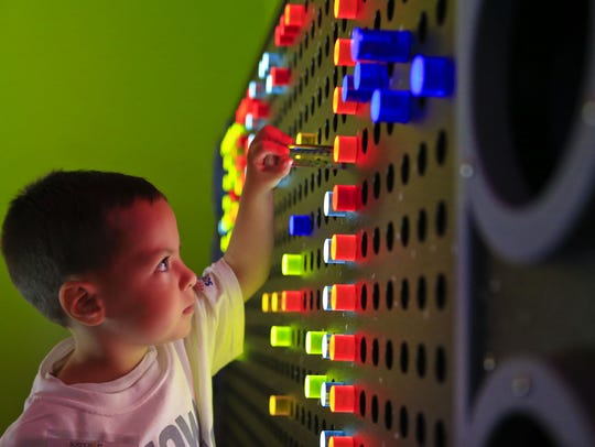Samuel Schmitt, 4, plays with light inside the Color