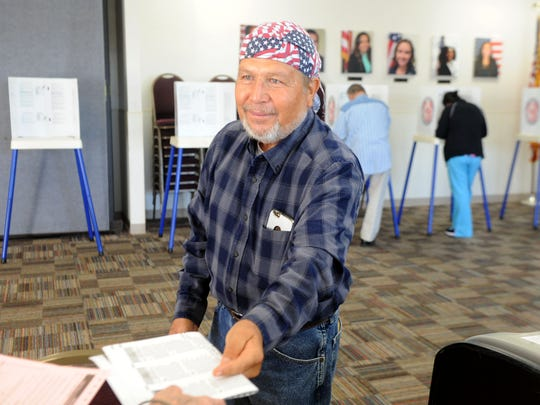 Nicardo Guzman, (cq) hands in his ballot after voting at the Boys & Girls Clubs of Oxnard and Port Hueneme. The polling place had a steady flow of voters.