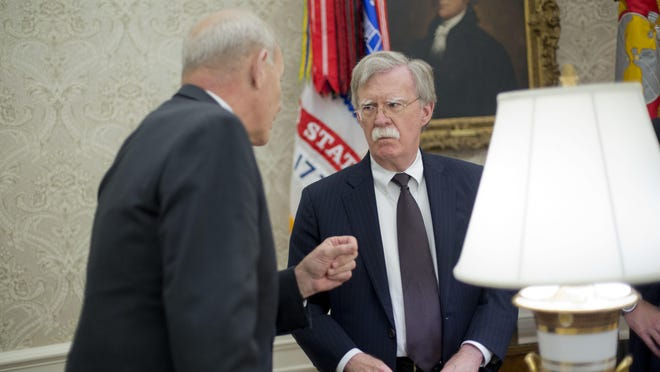 White House Chief of Staff John Kelly, left, talks with, White House National Security Advisor, John Bolton, center, in the Oval Office of the White House in Washington during President Donald Trump's meeting to discuss potential damage from Hurricane Michael, Wednesday, Oct. 10, 2018.
