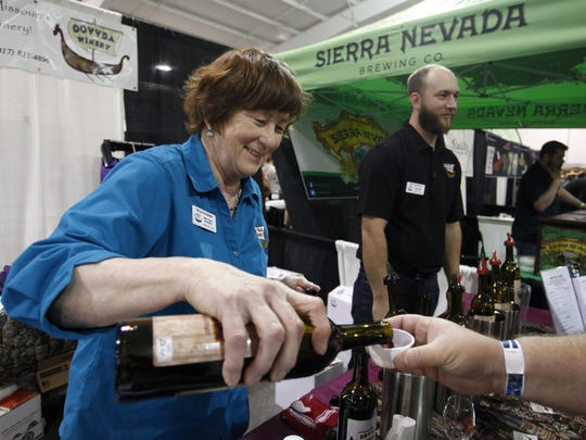 Fran Overboe, part owner of OOVVDA Winery, pours a sample of wine at a local food festival. Springfield-based OOVVDA makes fruit wines and wines from local grapes.
