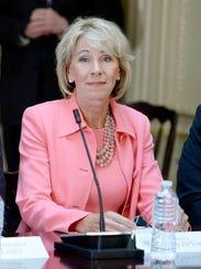 Secretary of Education Betsy DeVos listens as Pres.