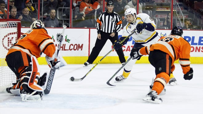 Predators forward Filip Forsberg, center, shoots against Flyers goalie Michal Neuvirth, left, who is gets some help from teammate Radko Gudas in the first period Friday.