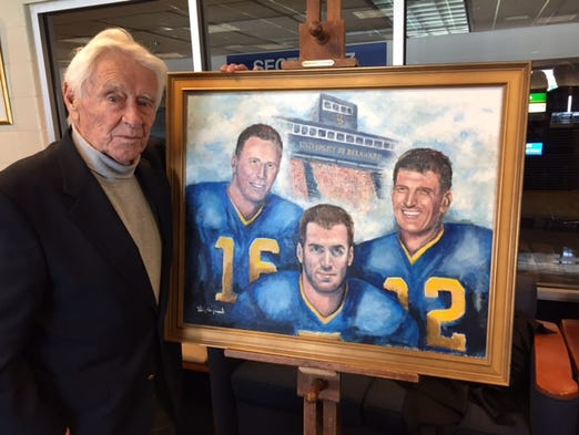 Former UD coach Tubby Raymond shows off his painting