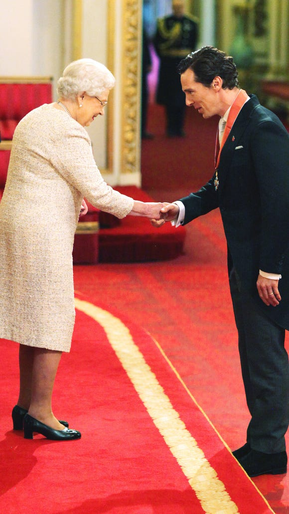 Benedict Cumberbatch, right, receives CBE from Queen