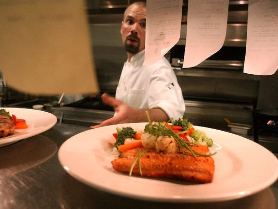 A chef at Mulligan's Pub & Sports Club fields orders while working in the restaurant's kitchen. The restaurant is one of few open on Christmas.