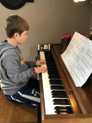 A piano student from the St. Peter's Community Arts Academy practices with his instructor on the phone.