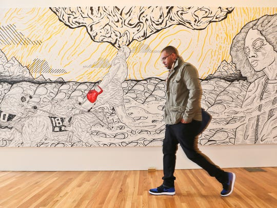 Nimbus founder Stacey Ward walks past a mural that features iconic figures such as Muhammad Ali as well as horse racing.