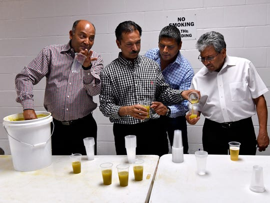 Men share a homemade drink made from sugar cane, lime and ginger during a break from dancing Friday in the Round Building at the Taylor County Expo Center. The building was packed with attendees celebrating the Saturday's marriage of Upasna and Amit Bhakta.