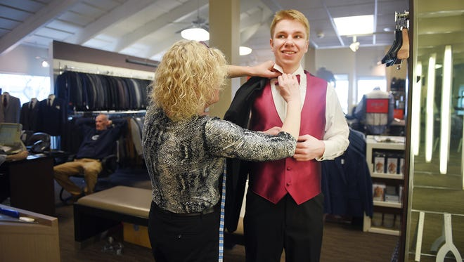 Men's Wearhouse store operations, Lori Swift, helps Brandon Valley High School senior Sam Stoltenburg try on his tuxedo the day before prom, Thursday, April 12, at Men's Wearhouse in Sioux Falls. Brandon Valley administrators decided to move their prom up from Saturday to Friday because of the weather.