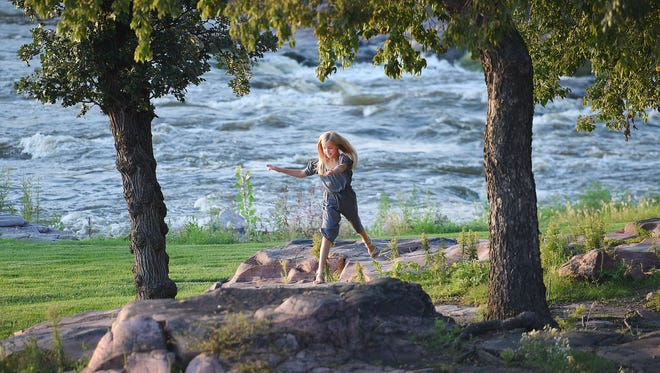 Charlotte Hultgren, 10, leaps from rock to rock in Falls Park in Sioux Falls.