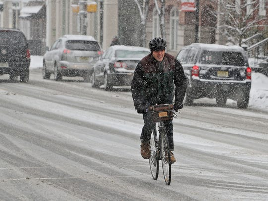 A man pedals on a bicycle as a steady snow falls in Morristown on Thursday, March 5, 2015.