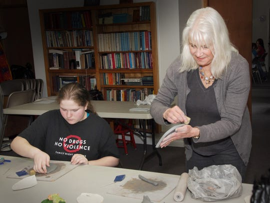 """Ash Creek Arts Center Spring Summer Art Camp student Jessie Welborn, 15, works with instructor Kathy Lord on a clay """"bug habitat"""" art project."""