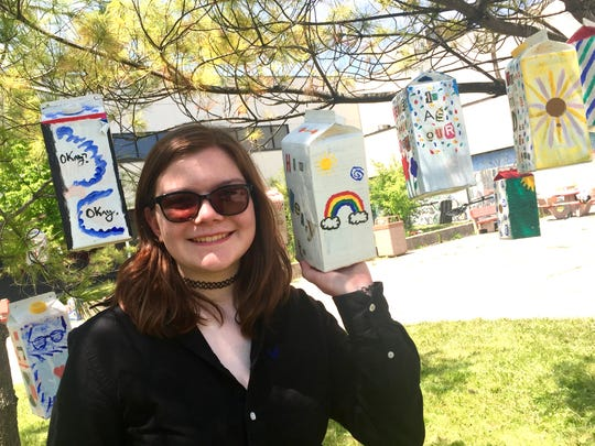 """Regina McManaman, 16, from West Bloomfield High School created this birdhouse from a recycled milk carton. Hers reads: """"How dreary to be somebody,"""" by Emily Dickinson."""