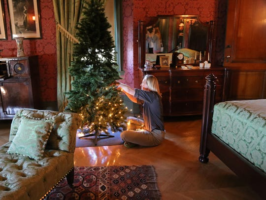 Hannah Weimer, of the Biltmore Estate floral department, decorates a Christmas tree in the Damask Room.