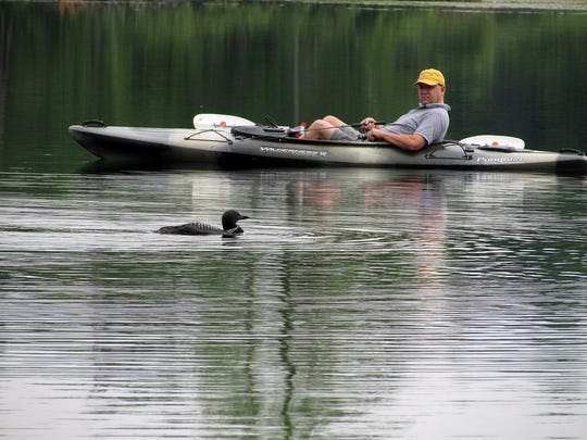 A loon visits son-in-law Andy as he fishes from his kayak.