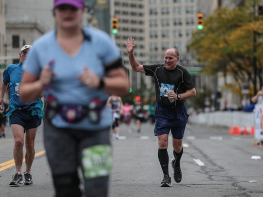 Mark Bauman of Flint raises his hand while coming to the finish line to complete his 40th full marathon during the 40th Annual Detroit Free Press/Chemical Bank Marathon in Detroit on Sunday, Oct. 15, 2017.