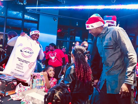 Detroit Pistons power forward Anthony Tolliver hands out gifts at a party for families and children at Little Caesars Arena's Heritage Hall in Detroit on Sunday, Dec. 17, 2017, part of the team's Season of Giving program to give back.
