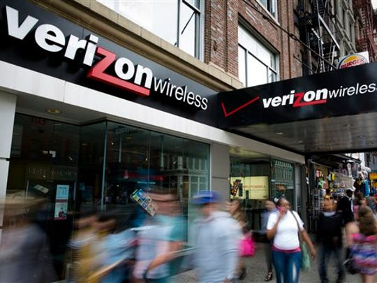 In this June 6, 2013, file photo, pedestrians pass a Verizon Wireless store on Canal Street in New York.
