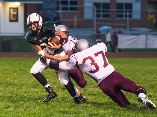 James Buchanan's Colby Bradshaw (24) tries to break past Shippensburg's Dylan Jumper (14) and  Nicholas Welts (37) during a football game  on Friday, Sept. 30, 2016. Shippensburg defeated James Buchanan 66-0.