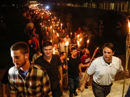 Peter Cvjetanovic (R)  and other White nationalists march with torches through the UVA campus in Charlottesville on Friday, August 11, 2017. (Via OlyDrop)
