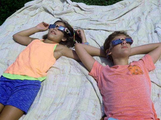 Siblings Maggie, 8, and Cooper Sentz, 13, of York Township watch the eclipse at St. Johns Blymire United Church of Christ in York Township Monday, Aug. 20, 2017. Former county parks employee and astronomer Jeri Jones brought his telescope to for people to watch the eclipse. Over 100 people showed up for the informal watch party. Bill Kalina photo