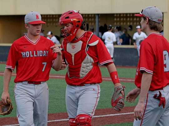 Holliday's Blake Gray, left, Jake Turner and Ryan Case head to the huddle during a change over in the game against Henrietta Tuesday, April 17, 2018, in Henrietta.