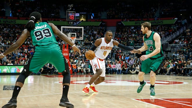 Atlanta Hawks forward Paul Millsap (4) drives against Boston Celtics forward Jae Crowder (99) and center Tyler Zeller (44) in the second quarter of their game at Philips Arena.