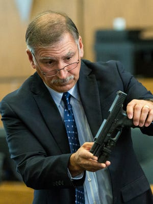 Prosecution's expert witness, Steve P. Guerra, New Mexico Department of Public Safety firearms tool marks, and gunshot residue examiner, shows the jury a semiautomatic glock on Friday, May 27, 2016,  during the Tai Chan trial at 3rd Judicial District Court.