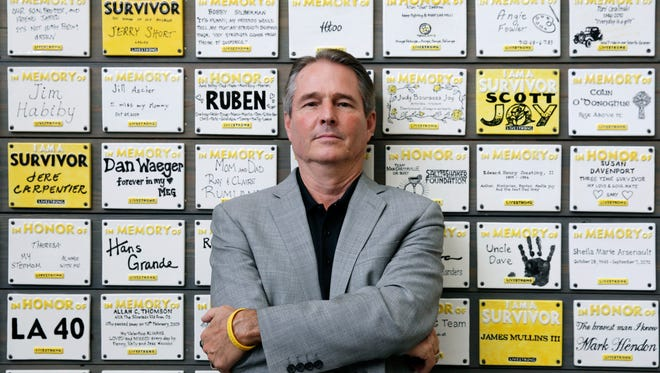 Livestrong President Greg Lee in front of wall of plates honoring cancer victims and survivors.