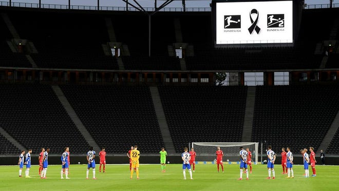 Players observe a minute's silence to commemorate the victims of the coronavirus pandemic prior to the German Bundesliga soccer match between Hertha BSC Berlin and 1. FC Union Berlin in Berlin, Germany, Friday, May 22, 2020. The German Bundesliga is the world's first major soccer league to resume after a two-month suspension because of the coronavirus pandemic.