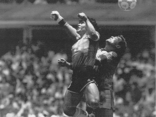 FILE - In this June 22, 1986 file photo Argentina's Diego Maradona, left, beats England goalkeeper Peter Shilton to a high ball and scores his first of two goals in a World Cup quarterfinal soccer match, in Mexico City. FIFA says Maradona will represent Argentina in the State Kremlin Palace, in Moscow, on Dec. 1, 2017, where all eight World Cup-winning nations will send a playing great to assist in the World Cup draw. (AP Photo/El Grafico, Buenos Aires, File)