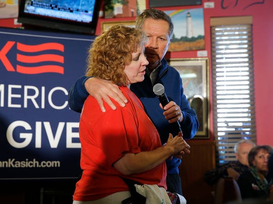 Julie McBride, a server at Applewood House of Pancakes in Pawleys Island, South Carolina talks with John Kasich about not having health insurance during a Feb. 11 town hall.