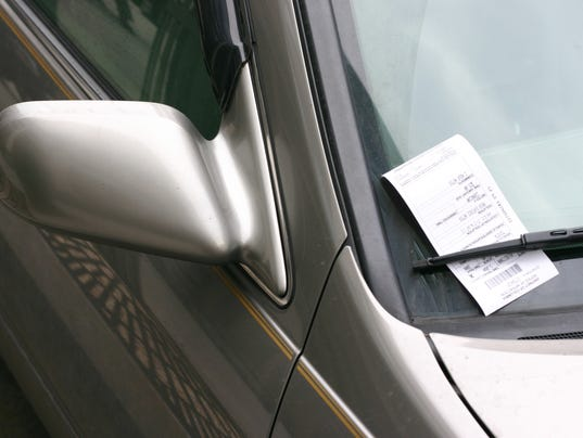 A silver car with a parking ticket on the window