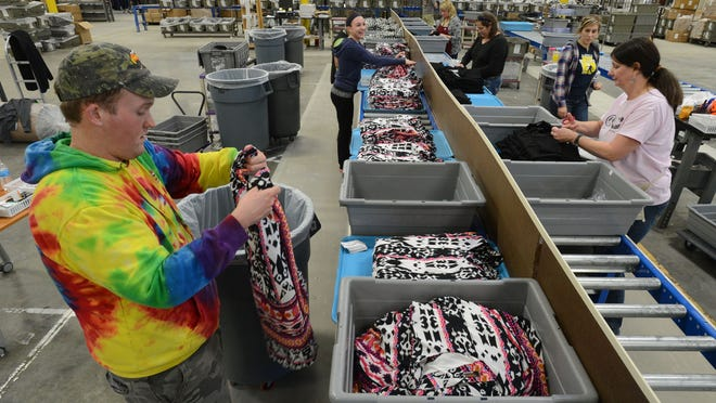 Mark Sigmon, left, retail line processor, and Roni Lay, line leader, sort merchandise at the new South Moon Under distribution facility in Salisbury.