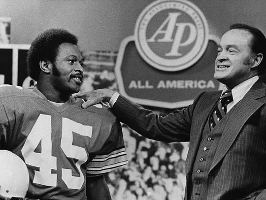 In this Dec. 8, 1975, file photo, comedian Bob Hope, right, talks with Ohio State All-America football player and Heisman Trophy winner Archie Griffin during taping of Hope's Christmas program in New York.