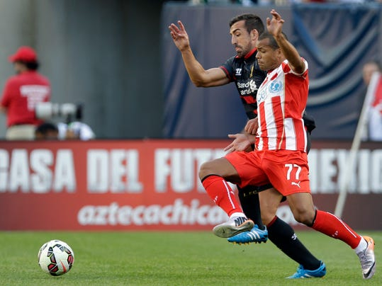 Liverpool FC defender Jose Enrique, left, and Olympiacos forward Mathieu Dossevi (77) battle for the ball during the first half of an International Champions Cup soccer match in Chicago, Sunday, July 27, 2014. (AP Photo/Nam Y. Huh)