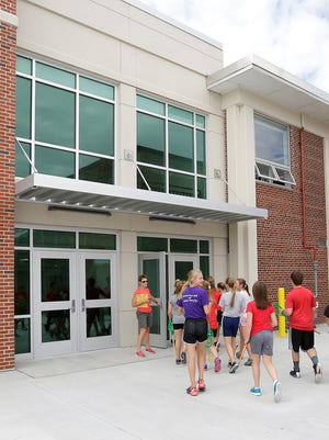 Lomira High School students enter part of the new building, from the new football field at Lomira High School. Because the field is artificial turf and requires less maintenance, physical education classes can use it without the fear of damaging it.